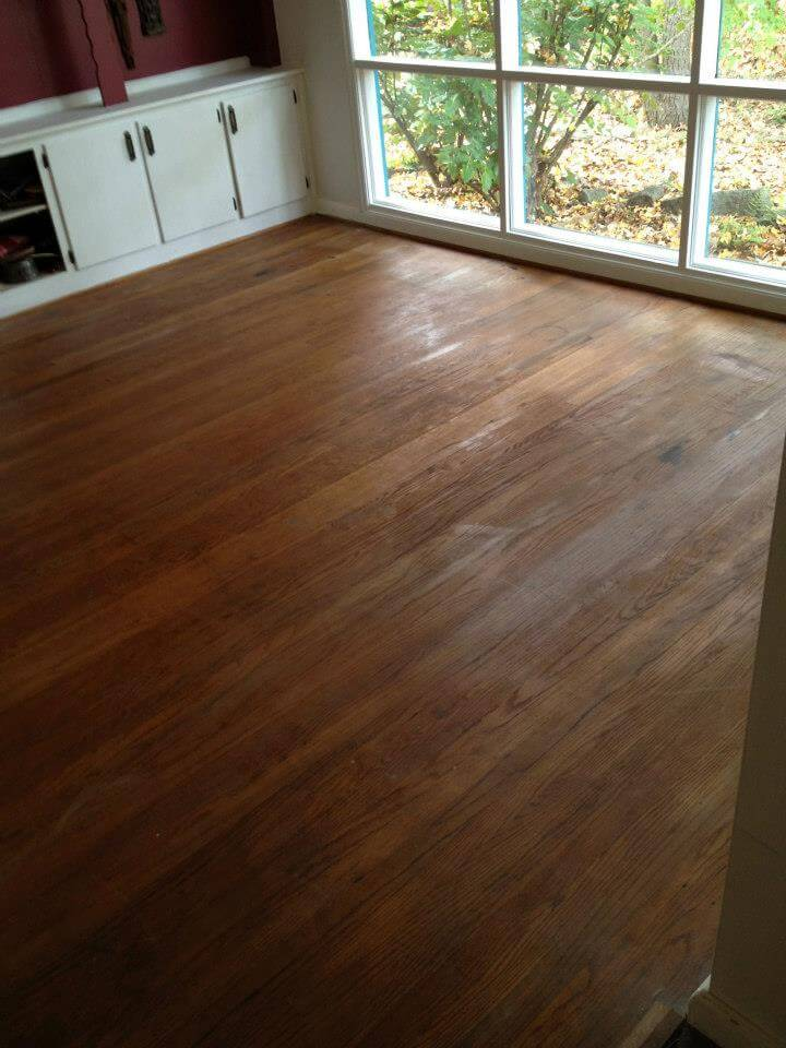 a damaged hardwood floor that needs to be refinished