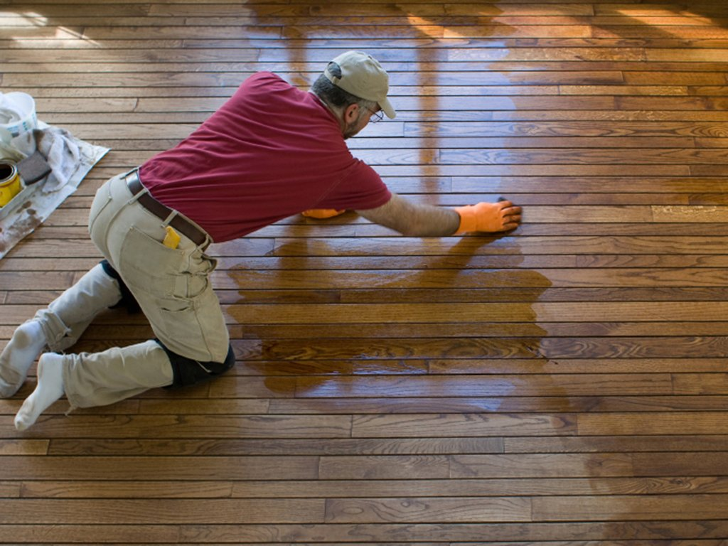 a detroit floor refinisher hard at work updating a wood floor.